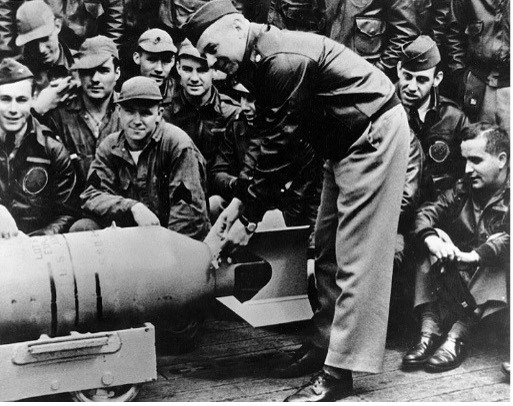 A photo of General Doolittle wiring a Japanese medal to a bomb prior to a raid on Japan
