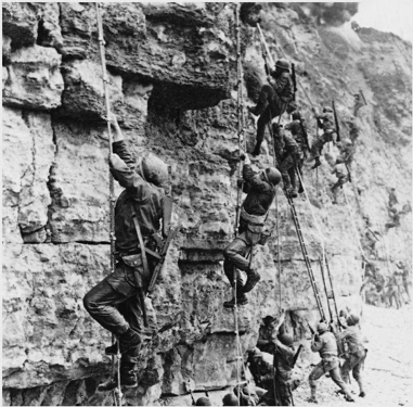 A black and white photo of D-Day soldiers climbing Point Du Hoc