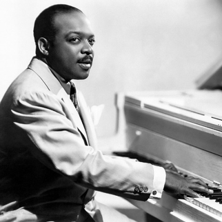 A portrait of Count Basie at his piano.