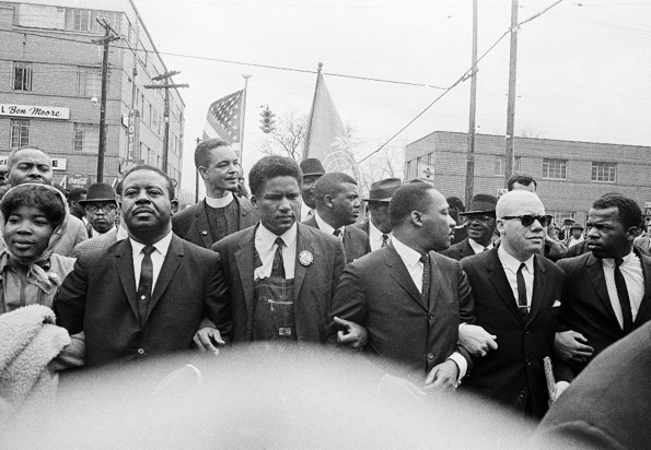 Dr. Martin Luther King Jr. locks arms with Rev. Ralph Abernathy, James Foreman, King, Jesse Douglas Sr., and John Lewis as they lead a crowd on a march through the streets of