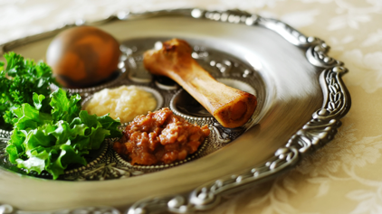 A lamb shank bone sits on a silver Seder plate