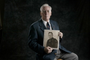 Bud Lomell poses with a portrait from his days in the Army.