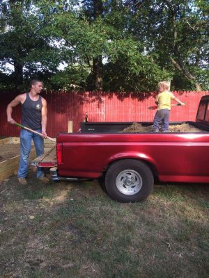 Brother Flowers working on the farm with his grandfather's red Ford pickup truck