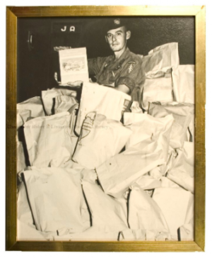 A photograph (in a gold-painted frame) of a United States Vietnam War soldier in the middle of a pile of Masonic Gift Packages.