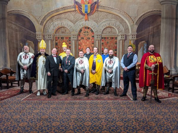 A cast of Scottish Rite Masons poses in front of their production set.